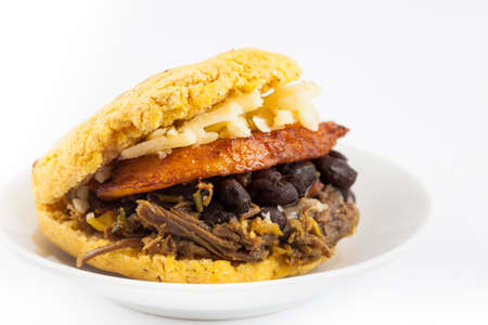 Arepas filled with shredded beef, black beans, plantain and cheese served in a white dish on white background