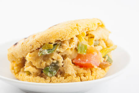 Arepas filled with scrambled eggs served in a white dish on white background 写真素材 - 106263817