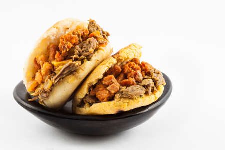 Arepas filled with shredded beef and pork rind served in a black ceramic dish on white background 写真素材