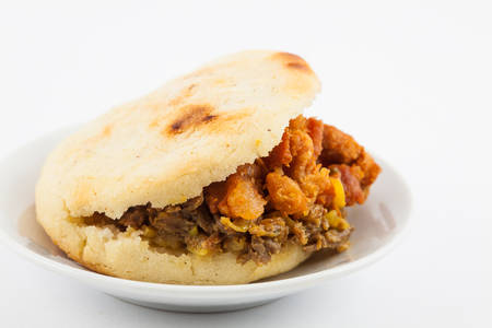 Arepas filled with shredded beef and pork rind served in white dish on white background 写真素材