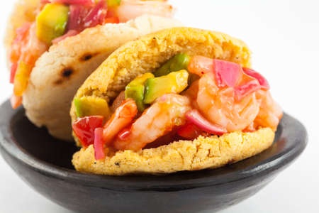 Arepas filled with shrimp ceviche served in a black ceramic dish on white background