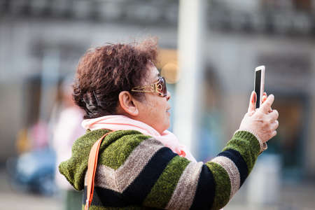 Asian tourists using their cellphones to take pictures at Dam Square in Amsterdam Banque d'images - 117152012