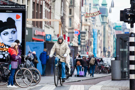 AMSTERDAM, NETHERLANDS- MARCH, 2018: Cyclist in a cold early spring day at the Old Central district of Amsterdam