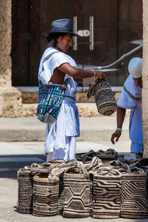 Two Arhuaco men dressed with their traditional clothes selling traditional bags in Cartagena de Indias Editorial