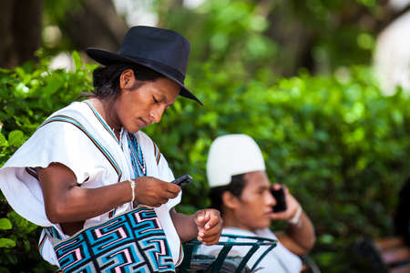 Two Arhuaco men dressed with their traditional clothes using their cellphones in Cartagena de Indias Stock fotó - 117152237