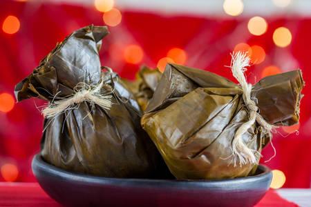 Traditionelles kolumbianisches Tamale, wie es in der Region Tolima über einem weihnachtlichen roten Hintergrund hergestellt wird