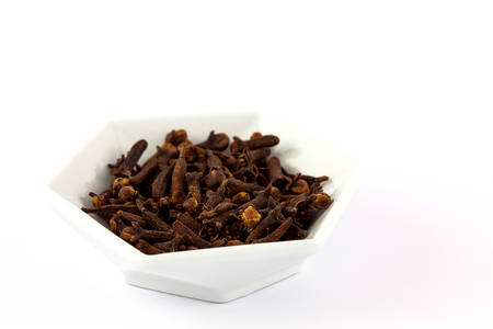 Spice cloves in a white ceramic dish isolated on white background Stock Photo