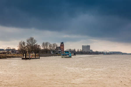 Ferry navigating on the Elbe river in a cold cloudy winter day in Hamburg