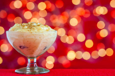 Traditional Colombian dessert made of rice and milk called arroz de leche on a christmas red background