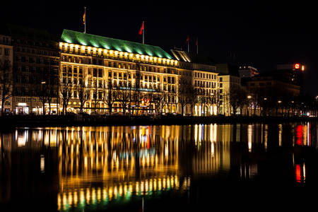 The Fairmont Hotel Vier Jahreszeiten located on the western side of the Inner Alster Lake shore at night time Editorial