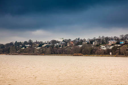 Beautiful houses and beaches on the banks of Elbe river in Hamburg on a cold end of winter day