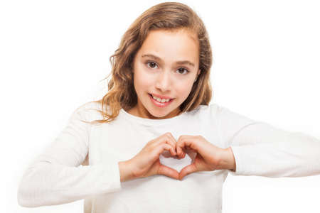 Young girl looking at camera showing heart gesture with two hands isolated on white background Banco de Imagens