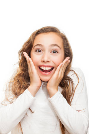 Smiling young girl looking happily surprised with hands on her chin isolated on white background Stockfoto