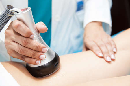 Doctor performing an  ultracavitation treatment on a young female patient leg