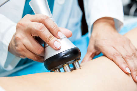 Doctor performing a radiofrequency treatment on a young female patient leg