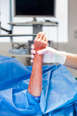 Doctor disinfecting the hand of a patient prior to a hand surgery