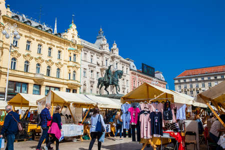 People at a street market in Zagreb main square in a beautiful early spring day Редакционное