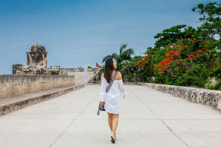 Beautiful woman on white dress walking alone at the walls surrounding the colonial city of Cartagena de Indias