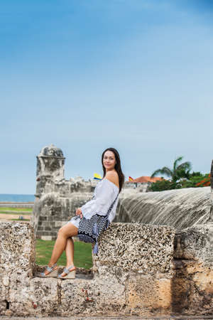 Beautiful woman on white dress sitting alone at the walls surrounding the colonial city of Cartagena de Indias Banco de Imagens