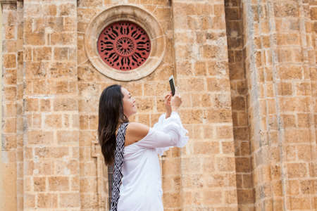 Beautiful woman taking pictures of the San Pedro Claver church located in the walled city of Cartagena de Indias Banco de Imagens