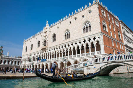 Tourists sailing in the gondola on the Grand Canal in Venice in front of the Doge Palace