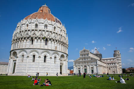 Tourists at the Pisa Baptistery of St. John in a beautiful early spring day