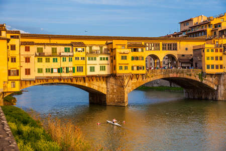 Golden hour at the Ponte Vecchio to medieval stone closed-spandrel segmental arch bridge over the Arno River in Florence