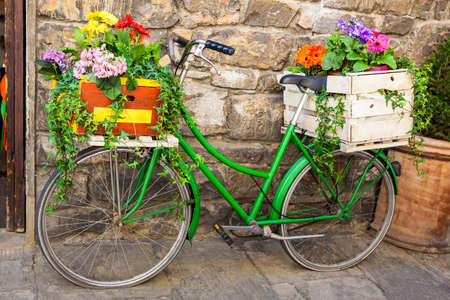 Green bicycle decorated with flowers parked in Florence