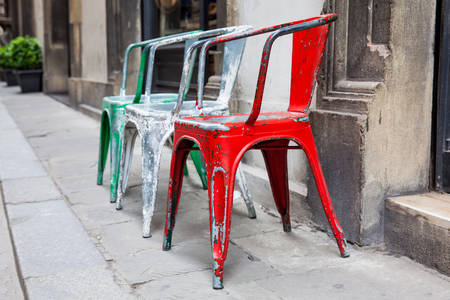 Three empty rickety colorful chairs at the historical streets of Florence