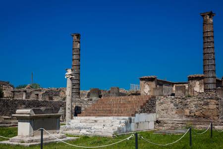 Ruins of the ancient Temple of Apollo with bronze Apollo statue in Pompeii