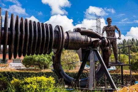 Beautiful industrial art sculpture by Jose Medardo Leguizamo of a man using coal to generate energy