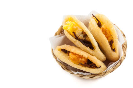 Arepa de huevo. Traditional Colombian fried arepa filled with egg and shredded meat on white background 写真素材
