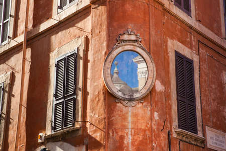 An small piece of the Santa Maria in Aquiro church reflected on a mirror at a corner of Piazza Capranica Zdjęcie Seryjne