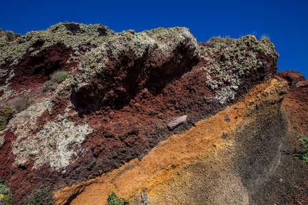 Red, orange and black stratified cliffs in Santorini Island