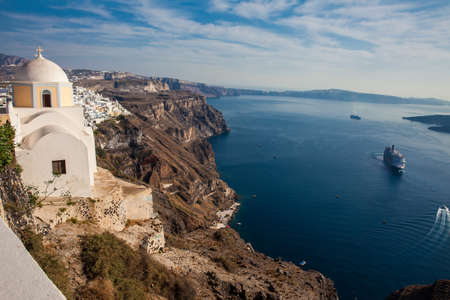 The Aegean sea and the Catholic Church of St. Stylianos in the city of Fira in Santorini Island