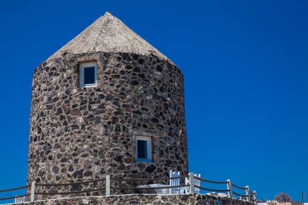 Antique windmill stone tower on the beautiful village of Imerovigli at Santorini Island