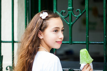 Young girl eating a traditional water ice cream typical of the Valle del Cauca region in Colombia