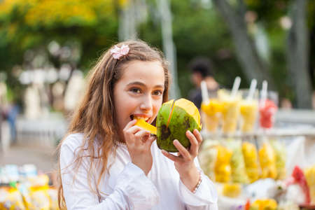 Beautiful young girl at Paseo Bolivar Square in the city of Cali eating tropical fruits in Colombia Stock Photo