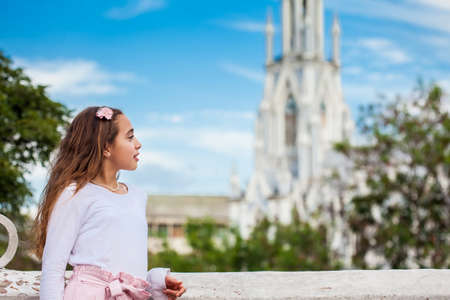 Beautiful young girl on the Ortiz Bridge looking at the famous gothic church of La Ermita in the city of Cali in Colombia