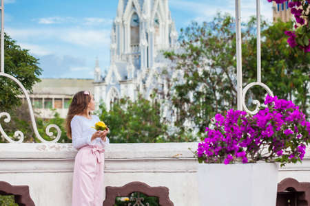Beautiful young girl on the Ortiz Bridge eating a mango in front of the famous gothic church of La Ermita built on 1602 in the city of Cali in Colombia