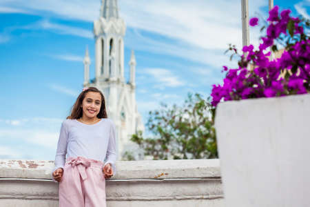 Beautiful young girl on the Ortiz Bridge with the famous gothic church of La Ermita in the city of Cali in Colombia