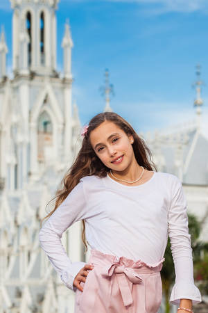 Beautiful young girl at the River Boulevard  in front of the famous gothic church of La Ermita built on 1602 in the city of Cali in Colombia