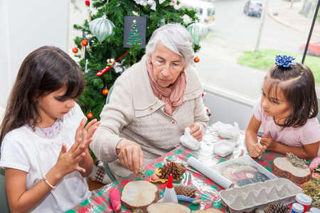 Grandmother teaching her granddaughters how to make christmas Nativity crafts - Real family Stock fotó