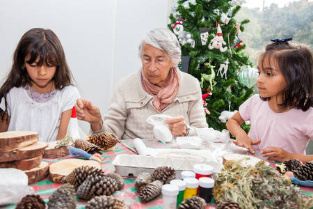 Little girls having fun while making christmas Nativity crafts with their grandmother - Real family