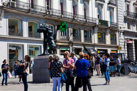 MADRID, SPAIN - MAY, 2018: Tourists and locals at the famous Puerta del Sol square looking at the iconic statue of the Bear and the Strawberry Tree which represents the coat of arms of Madrid