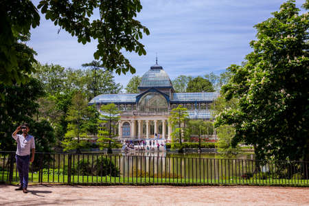 MADRID, SPAIN - MAY, 2018: Tourists taking a selfie in front of the beautiful Palacio de Cristal a conservatory located in El Retiro Park built in 1887 in Madrid Editorial