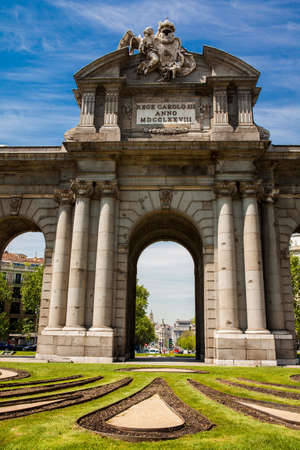 The famous Puerta de Alcala on a beautiful sunny day in Madrid City. Inscription on the pediment: King Carlos III year 1778