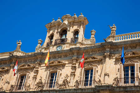 View of the beautiful antique buildings around Plaza Mayor an 18th century Spanish baroque public square surrounded by shops, restaurants and the town hall in Salamanca old city