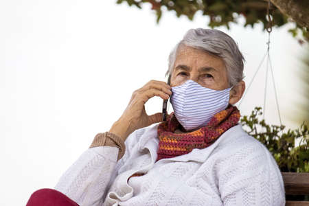 Senior woman outdoors using her cell phone wearing a home made face mask during the coronavirus quarantine de-escalation 写真素材