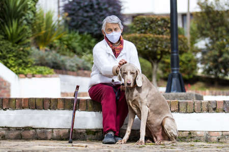 Senior woman wearing a home made face mask and enjoying some time outdoors with her pet during the coronavirus quarantine de-escalation 写真素材